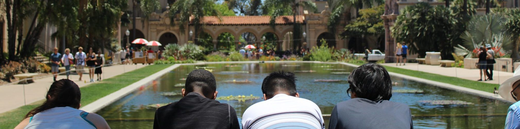 Family looking out over the serene waters of Balboa Park's Lily Pond.