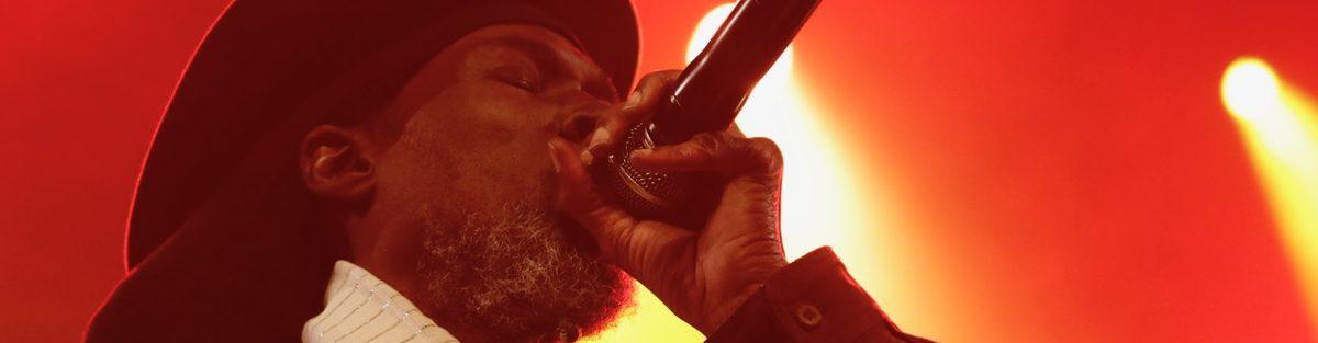 A close-up of music artist, Akae Beka, as he sings into his microphone.