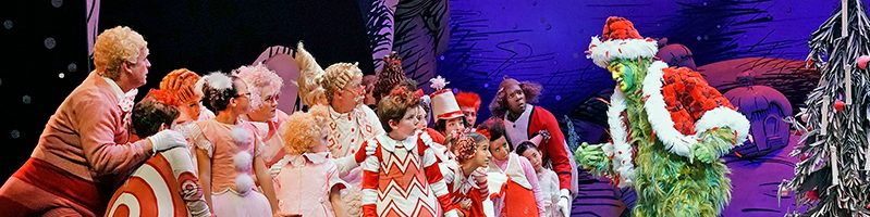 A still shot of The Old Globe Theater's How the Grinch Stole Christmas, as the Grinch towers over curious Who villagers.