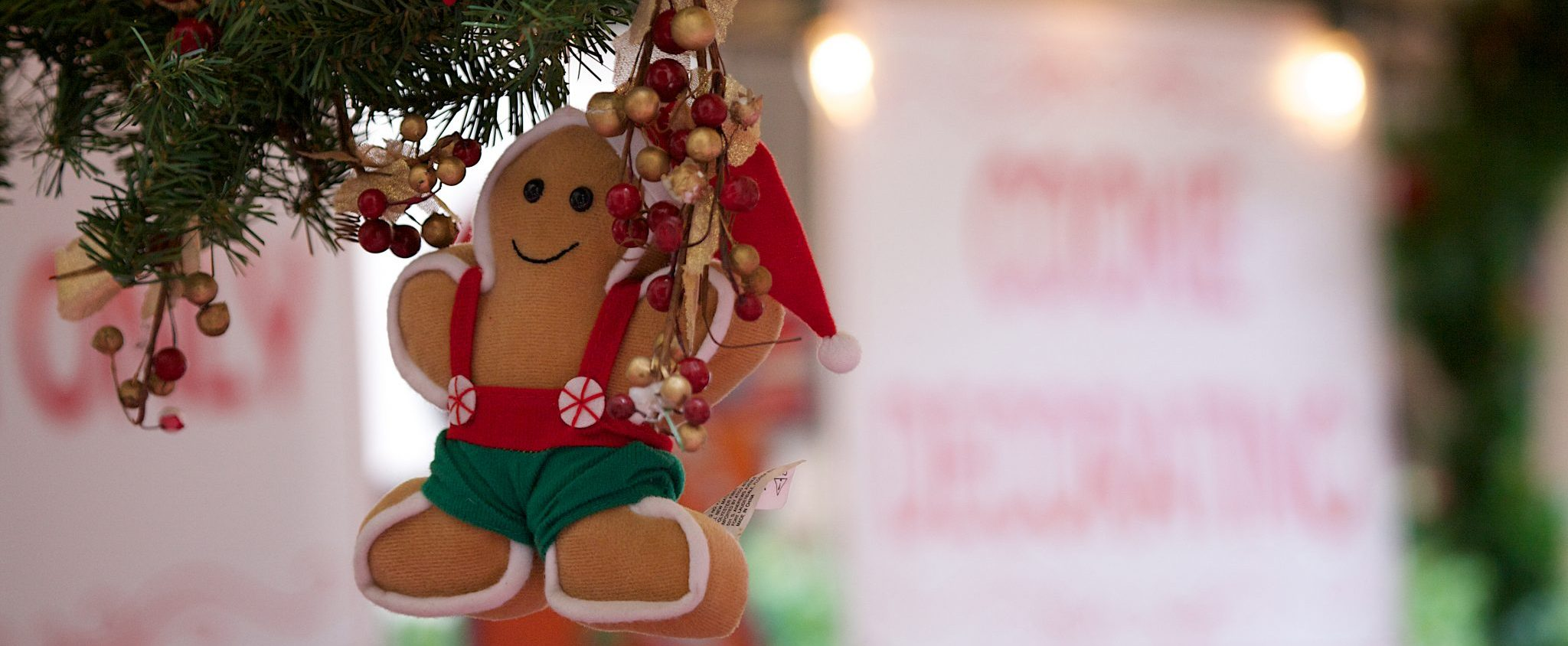 Gingerbread man ornament hanging from a Christmas tree.